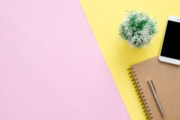 Office desk working space - Flat lay top view of a working space with white blank notebook page, plant tree and mock up phone on pastel background. Pastel pink yellow color background space concept.
