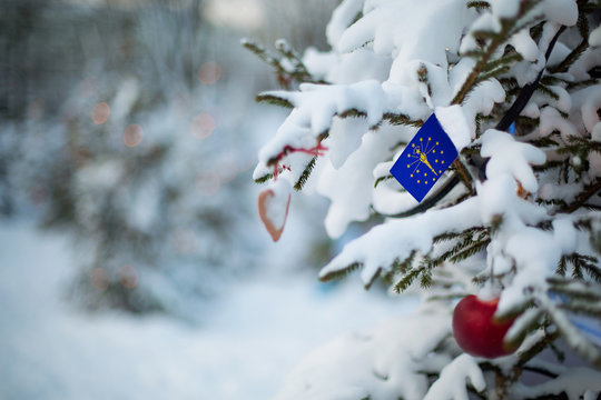 Indiana state flag. Christmas background outdoor. Christmas tree covered with snow and decorations and Indiana flag.  New Year / Christmas holiday greeting card.
