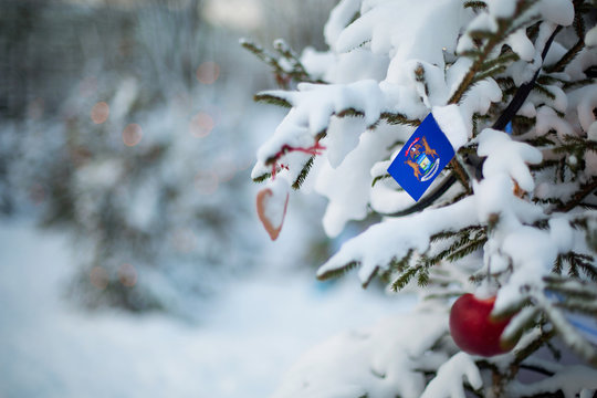 Michigan state flag. Christmas background outdoor. Christmas tree covered with snow and decorations and Michigan flag.  New Year / Christmas holiday greeting card.