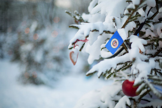 Minnesota state flag. Christmas background outdoor. Christmas tree covered with snow and decorations and Minnesota flag.  New Year / Christmas holiday greeting card.