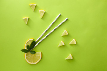 Flat lay composition with lemon slices and straws on color background