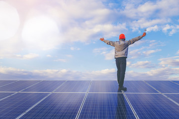 Electrical and instrument technician use wrench to maintenance electric system at solar panel field stand on solar panel and open arms