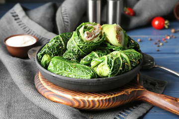 Pan with stuffed cabbage leaves on wooden board