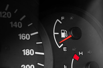 Low fuel readings on car dashboard. Horizontal photography