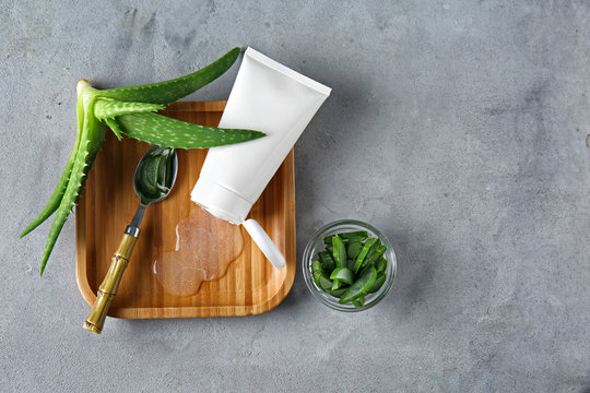 Tube with aloe vera gel and green plant on grey table