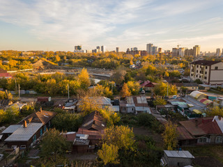 Autumn landscape on the city from the side of the ghetto with old dilapidated houses on the background of high multi-storey skyscrapers in the center with a blue sky and clouds on an autumnal day