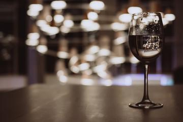 Glass with champagne lit by nightclub lights on dark background