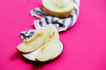 Close-up of melon and slices on a plate on the table