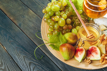 Grape, cheese, figs and honey with wine on wooden table