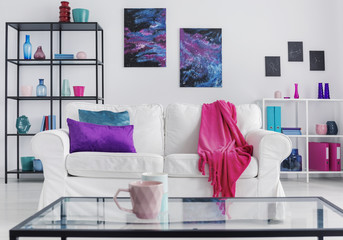 Pink mug on table in front of white settee with blanket in apartment interior with posters. Real photo