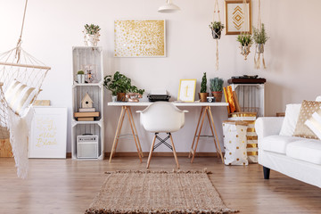 White chair placed by the desk with fresh plants and typewriter in real photo of bright living room interior with posters and rug on the floor