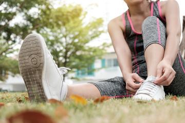Sport excercise running practice outdoor concept. Woman tight her sneaker shoe in park.