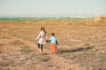 poor small girl and boy refugees walk in desert towards fencing with barbed wire