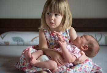 Little sister hugging her newborn sister on bed