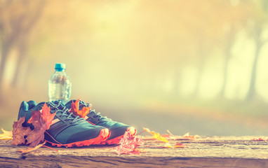 Blue sport shoes and water laid on a wooden board.