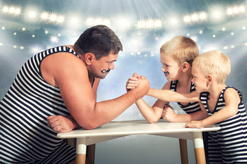 Family of strongman. The father of two sons in vintage costume of athletes compete in arm wrestling. Family look.