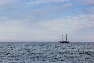 A black yacht boat in the sea with cloudy sky