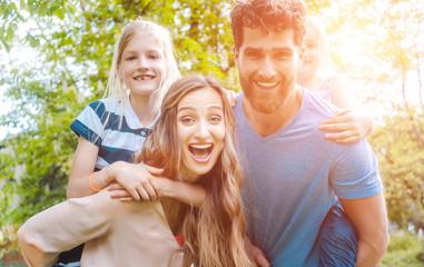 Familie hat Spaß zu viert, der Vater trägt die Töchter huckepack