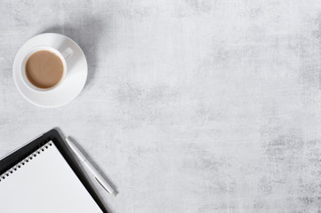 Minimalistic light background with notepad and cup of coffee