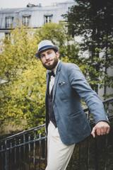 Homme style retro posant dans les escaliers et devant les immeubles parisiens, Montmartre, France
