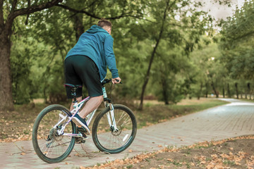 Young caucasian man biking through the abandoned path in the autumn park, casual sportswear. Dark hair, white earphones. Outdoors, yellow leaves on the ground, green trees.
