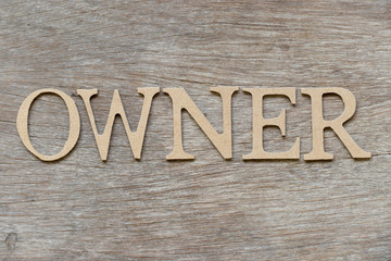 Alphabet letter in word owner on wood background