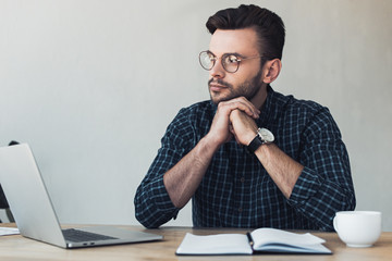 portrait of pensive businessman at workplace with laptop and notebook