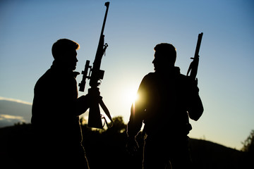 Hunting with partner provide greater measure safety fun and rewarding. Hunter friend enjoy leisure. Hunters friends gamekeepers with guns silhouette sky background. Hunters rifles nature environment