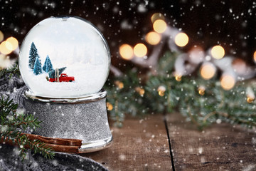Rustic image of a snow globe with old pick up tuck hauling a Christmas tree surrounded by pine branches, cinnamon sticks and a warm gray scarf with gently falling snow flakes and blurred background.