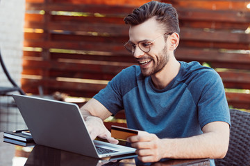 smiling handsome man shopping online with credit card and laptop at table at street cafe
