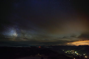 The stars of the Milky Way at night in the sky glow through the clouds. View of outer space in cloudy weather.