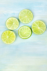 An overhead photo of many vibrant lime slices on a teal blue background with copy space