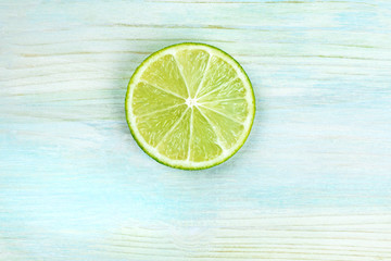 An overhead photo of a single lime slice on a teal blue background with copyspace