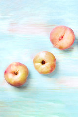 An overhead photo of vibrant organic flat saturn peaches, shot from above on a teal background with copyspace