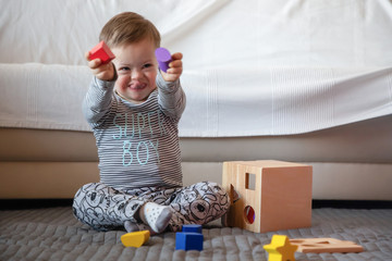 Portrait of cute boy with Down syndrome playing in home living room