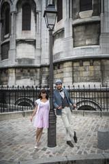 Amoureux dans la rue à Montmartre posant contre un lampadaire, Paris, France