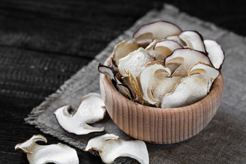 Dried boletus mushrooms in a wooden plate. Wooden background. Porcini