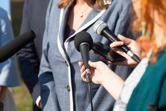 Journalists making media interview with businesswoman or female politician