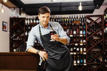 Male sommelier tasting red wine in cellar. Professional degustation expert