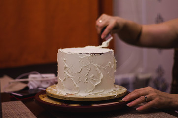 pastry chef covers the cake with white cream