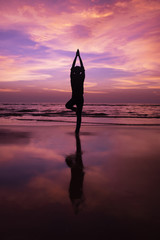Foto op Plexiglas Candy roze Silhouette of a young man meditating at sunset at beach