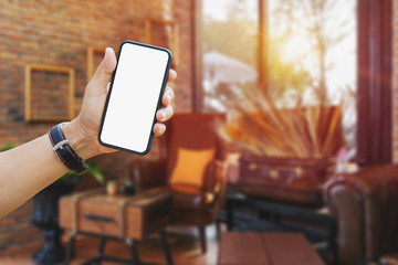 Mockup image of man's hands holding mobile phone with blank screen in modern cafe