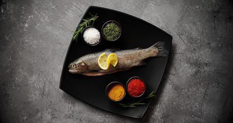From above shot of ceramic plate with assorted aromatic spices and fresh uncooked trout standing on surface of stone tabletop