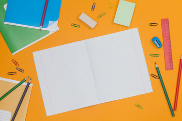 Open school notebook for your text over colorful supplies on orange background. Back to school concept with copy space. Flat lay. Top view.