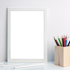 Photo of a white mockup frame with colorful pencils in a wooden toolbox on a desk