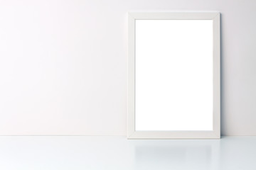Photo of a white mockup frame on white blank wall copy space background on a white desk