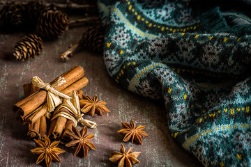Traditional Christmas spices (star anise, cinnamon sticks for festivity) and warm knitwear on rustic background
