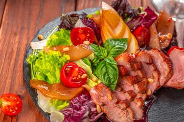 Tasty sliced roast duck breast with fresh vegetable salad closeup on a plate.
