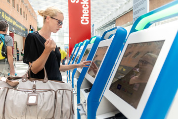 Casual caucasian woman using smart phone application and check-in machine at the airport getting the boarding pass. Modern technology on airport.