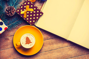 yellow cup of Cappuccino with cream Christmas tree and open book on wooden table near toys.
